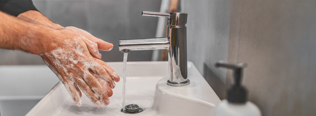 Man washing hands to avoid germs and COVID-19.
